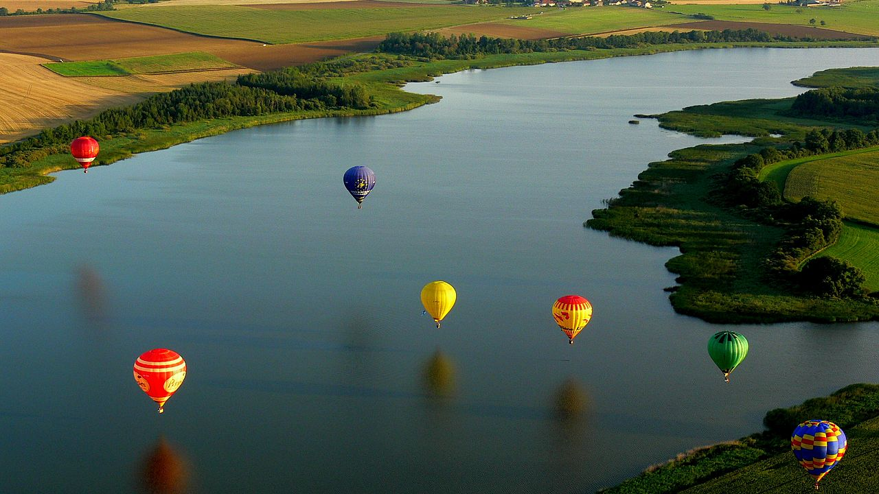 Hot Air Balloons over river landscape.